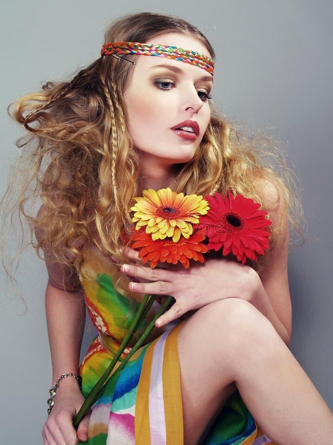 Schöne junge Frau hält bunte Blumen an stockfotografie
