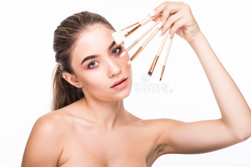 Schöne junge Frau hält die Make-upbürsten nahe attraktivem Gesicht Mode-Modell, das über weißem Hintergrund aufwirft lizenzfreie stockfotos