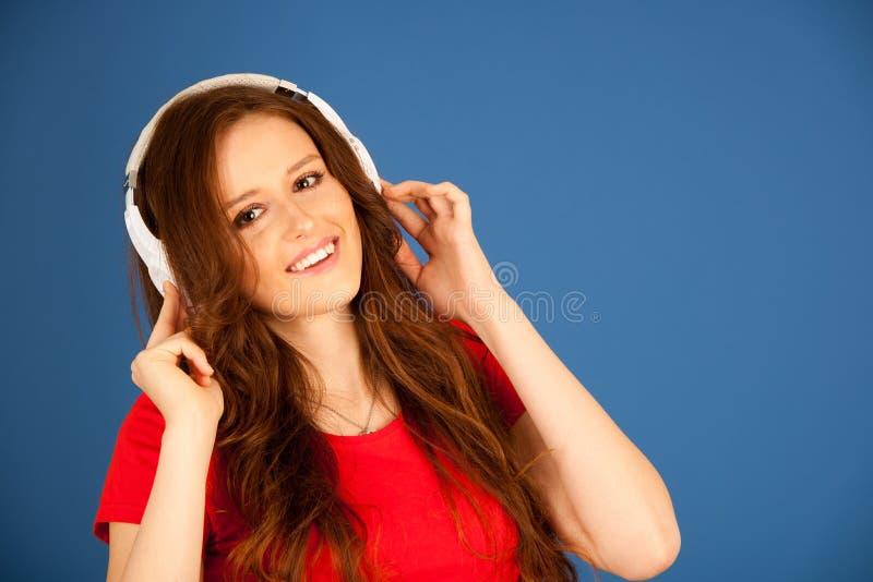 Schöne junge Frau hören Musik über vibrierendem Farbbac lizenzfreies stockfoto
