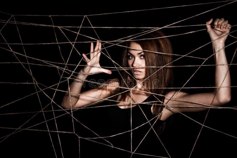 Schöne junge Frau hinter dem Netz von Seilen lizenzfreie stockfotografie