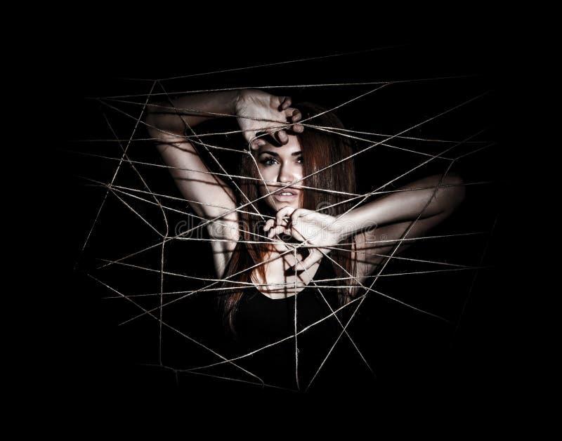 Schöne junge Frau hinter den verschachtelten Seilen stockfoto