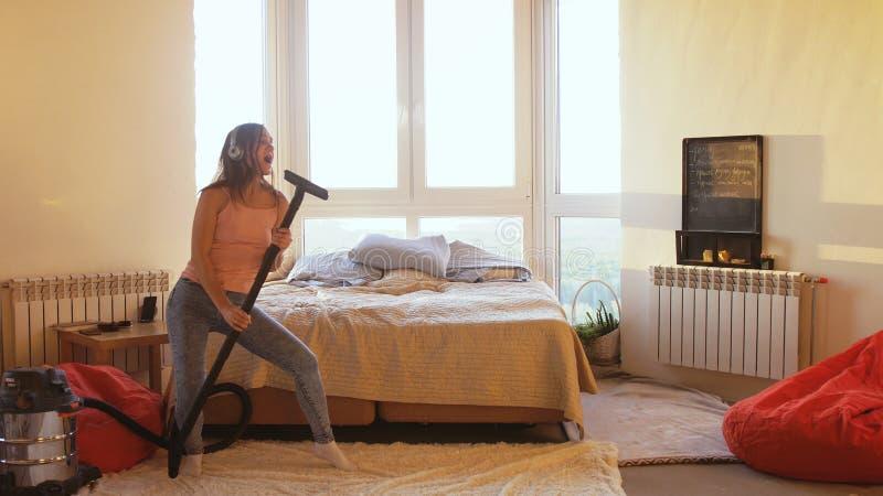 Schöne junge Frau hoovering den Boden zu Hause unter Verwendung des modernen Staubsaugers und hört Musik mit Kopfhörern lizenzfreie stockfotos