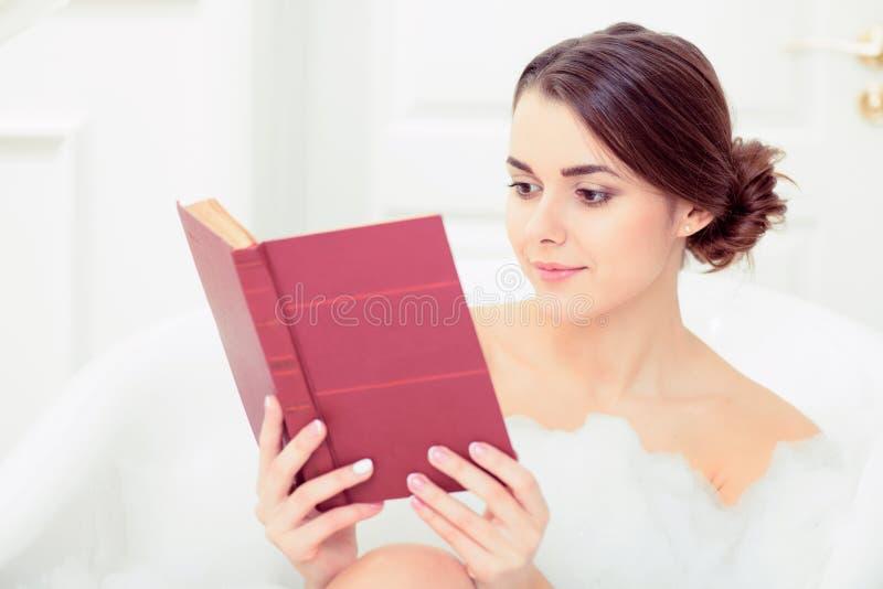 Schöne junge Frau im Bad mit einem Buch lizenzfreie stockfotos