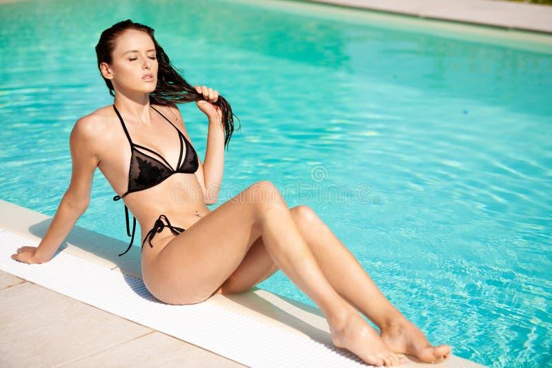 Schöne junge Frau im Badeanzug ein Sonnenbad nehmend nahe Pool stockfotografie