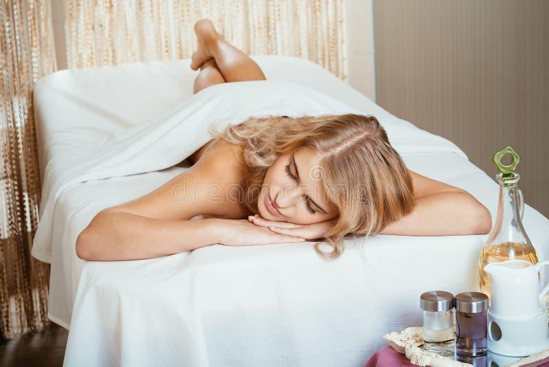 Schöne junge Frau im Badekurort, der auf Tabellenwartemassage sich entspannt stockfoto