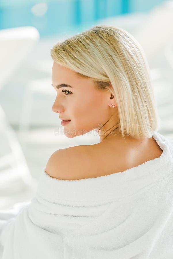 schöne junge Frau im Bademantel, der mit nackter Schulter sich entspannt stockfoto