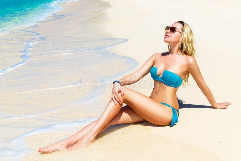 Schöne junge Frau im Bikini auf einem tropischen Strand lizenzfreie stockfotos