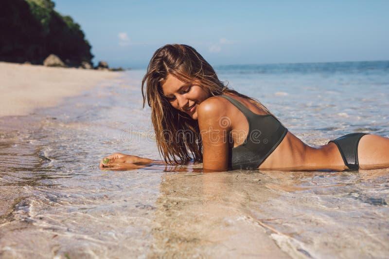 Schöne junge Frau im Bikini, der auf dem Strand liegt stockfotografie