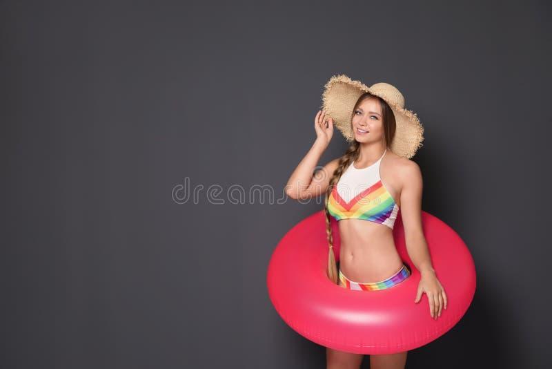 Schöne junge Frau im Bikini mit aufblasbarem Ring gegen dunklen Hintergrund lizenzfreie stockfotos