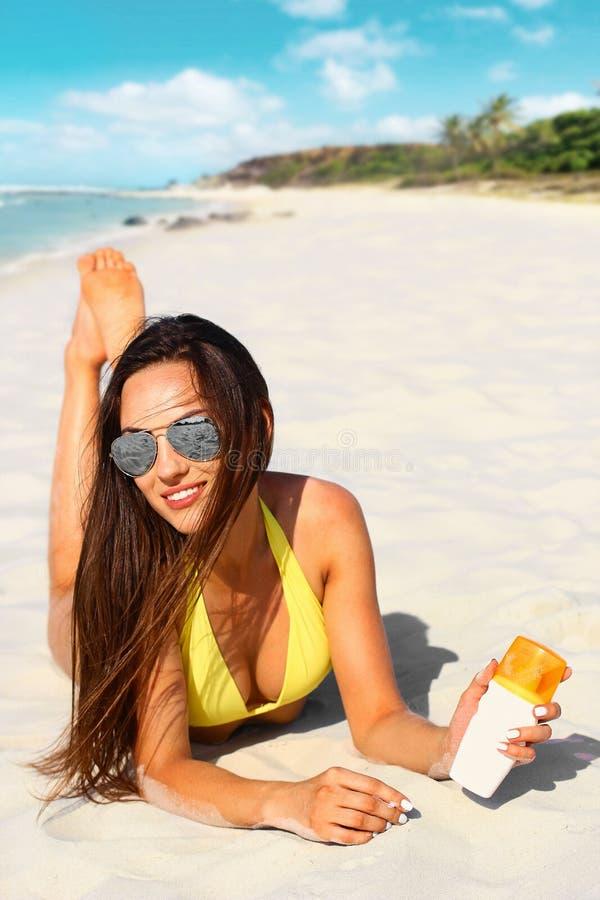 Schöne junge Frau im Bikini mit schützender Creme in der Hand auf dem Strand unter der Sonne lizenzfreies stockfoto