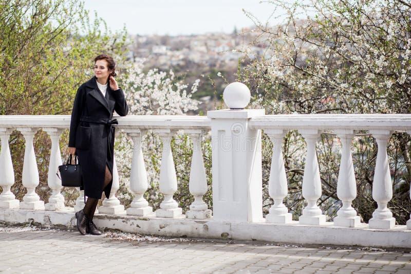 Schöne junge Frau im dunklen woolen Mantel in der Straße setzen im Frühjahr Zeit fest Mandelblumenblüten, tragender modischer Man lizenzfreies stockfoto