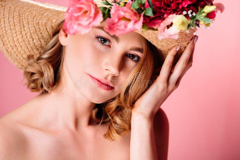 schöne junge Frau im Hut mit den Blumen, die Kamera betrachten lizenzfreie stockfotos
