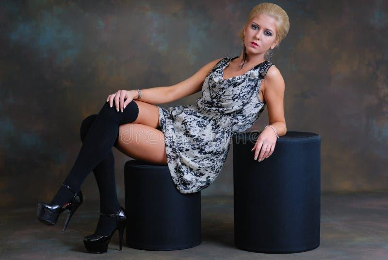 Schöne junge Frau im Kleid und in den Strümpfen lizenzfreies stockfoto