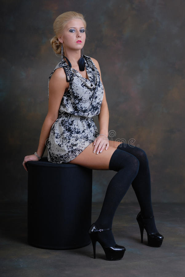 Schöne junge Frau im Kleid und in den Strümpfen stockbilder