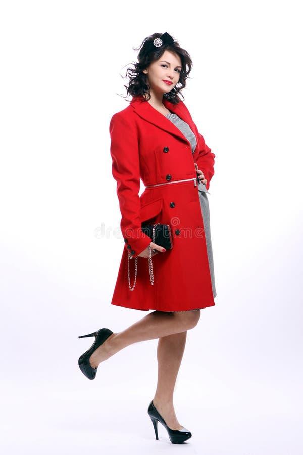Schöne junge Frau im roten Mantel lizenzfreie stockfotos