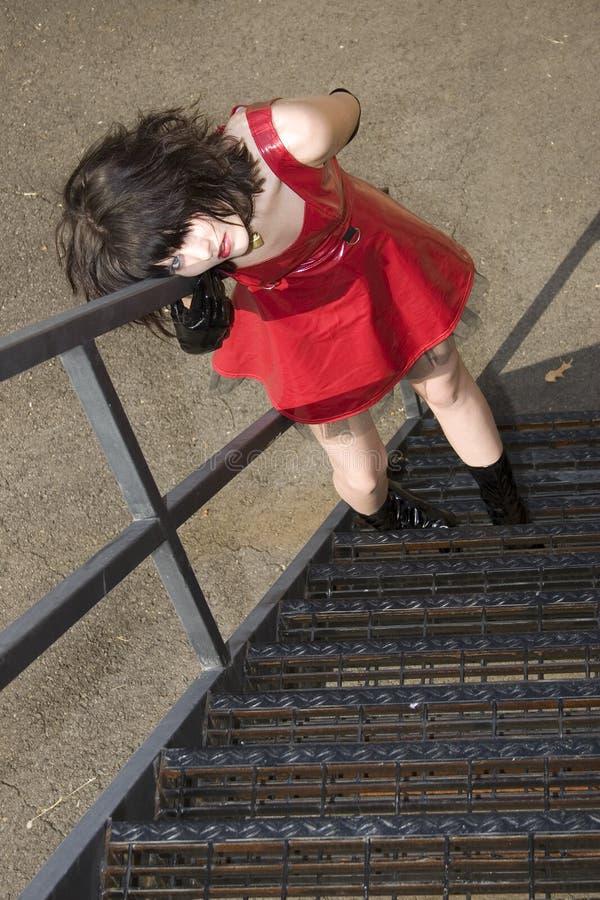 Schöne junge Frau im roten Vinylkleid auf Feuer-Entweichen lizenzfreies stockbild