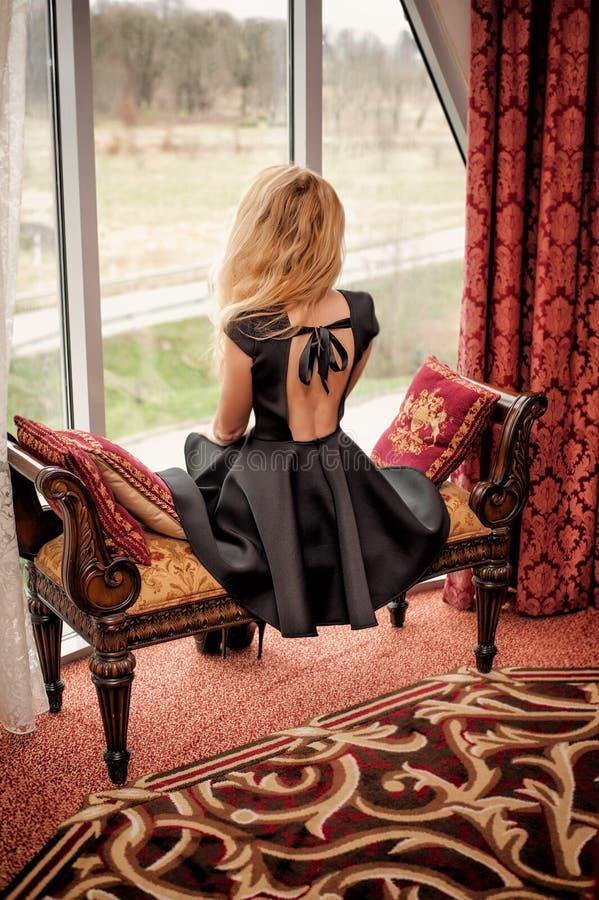 Schöne junge Frau im schwarzen Modekleid mit sitt des offenen Rückens stockfoto