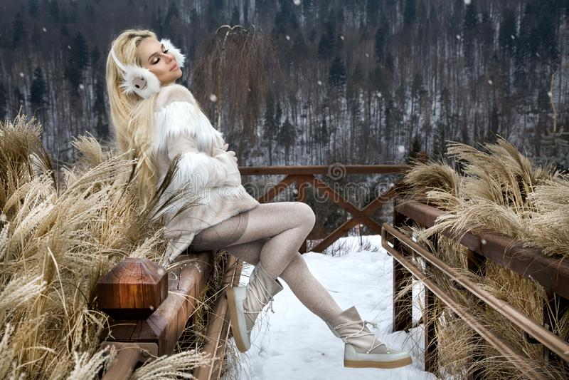 Schöne junge Frau im sexy Minikleid, stehend auf dem Schnee und der Ansicht der Berge stockbild