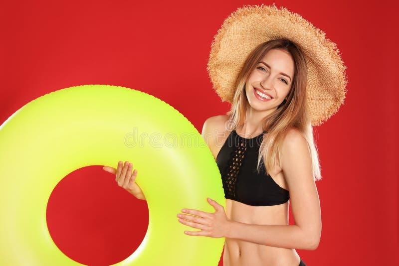 Schöne junge Frau im stilvollen Bikini mit gelbem aufblasbarem Ring lizenzfreie stockfotografie