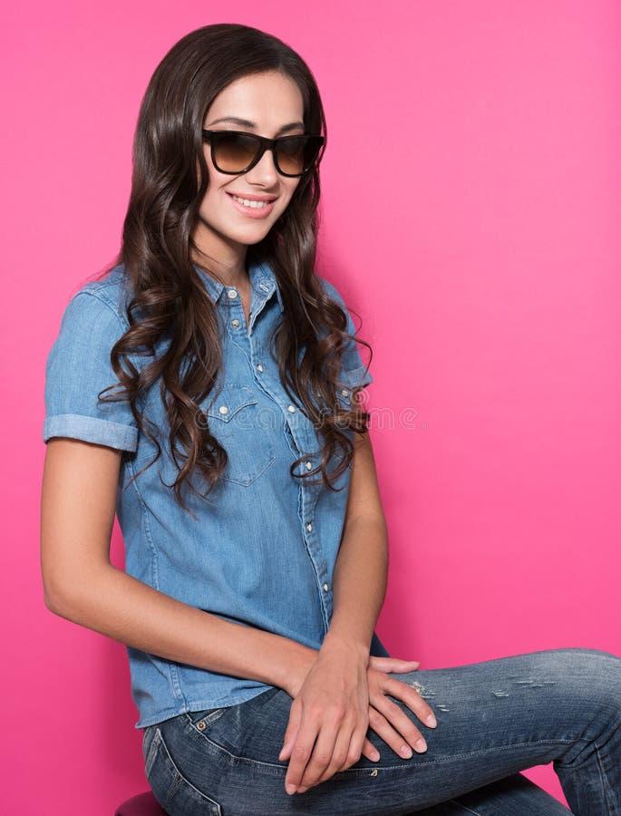 Schöne junge Frau im stilvollen Kleid und in der Sonnenbrille, die über rosa Hintergrund aufwirft stockfotos