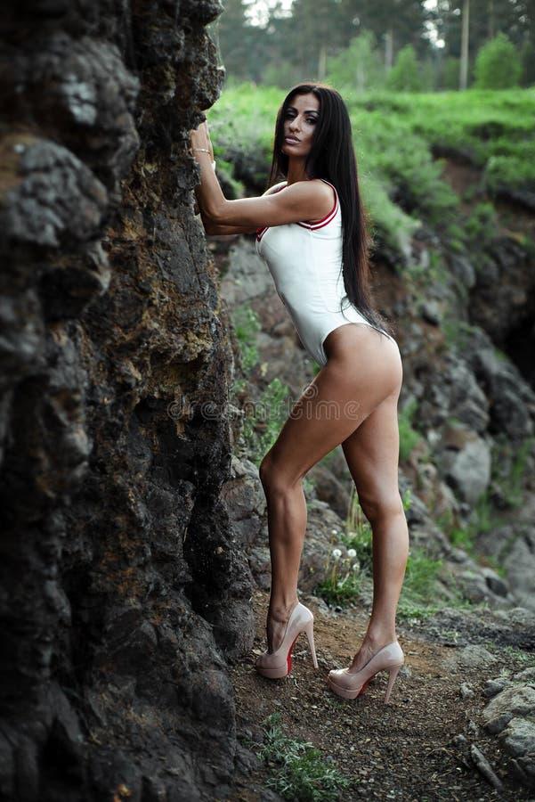 Schöne junge Frau im weißen Bodysuit mit den Fersen, die auf Steinhintergrund aufwerfen outdoor Gr?n stockfotografie