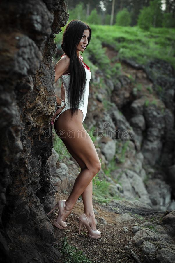 Schöne junge Frau im weißen Bodysuit mit den Fersen, die auf Steinhintergrund aufwerfen outdoor Gr?n lizenzfreies stockfoto