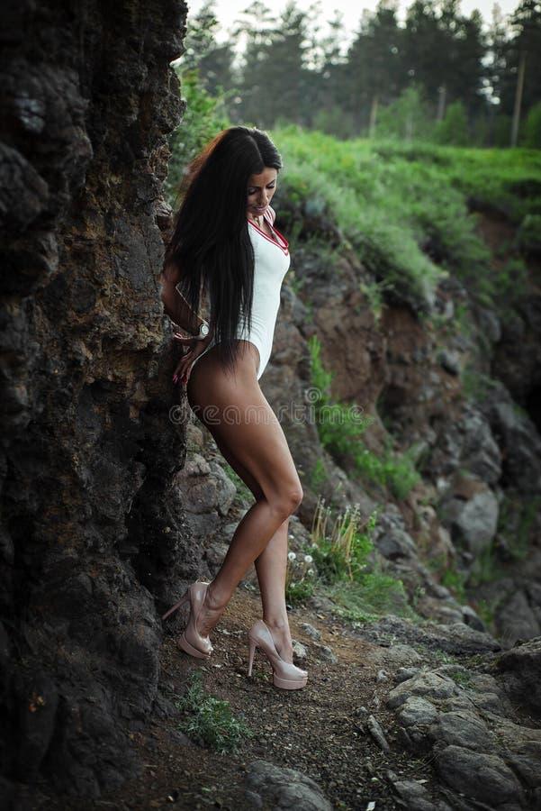 Schöne junge Frau im weißen Bodysuit mit den Fersen, die auf Steinhintergrund aufwerfen outdoor Gr?n stockbilder