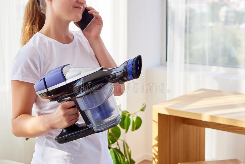 Schöne junge Frau im weißen Hemdholding-Staubsauger und Unterhaltung auf Mobiltelefon, Kopienraum Hausarbeit, Frühjahrsputz lizenzfreie stockbilder