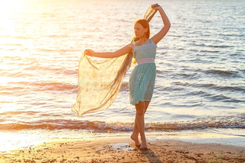 Schöne junge Frau im weißen Kleid durch das Meer in der Sonne lizenzfreie stockbilder