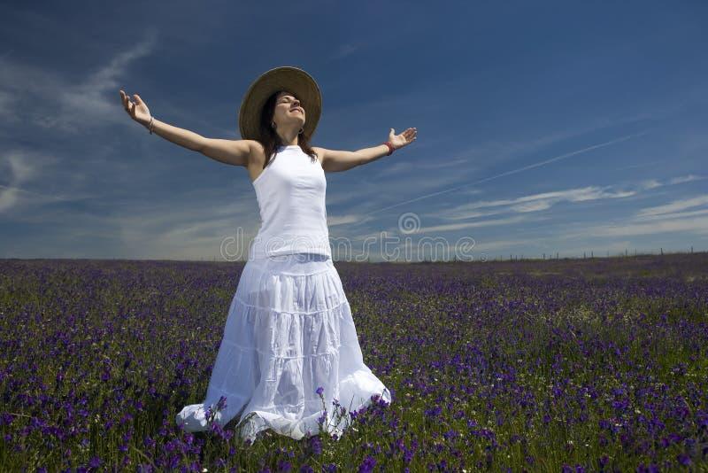 Schöne junge Frau im weißen Kleid mit den breiten Armen öffnen sich stockfoto