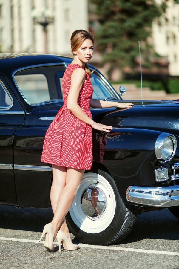 Schöne junge Frau im Weinlesekleid mit Retro- Auto lizenzfreie stockfotos