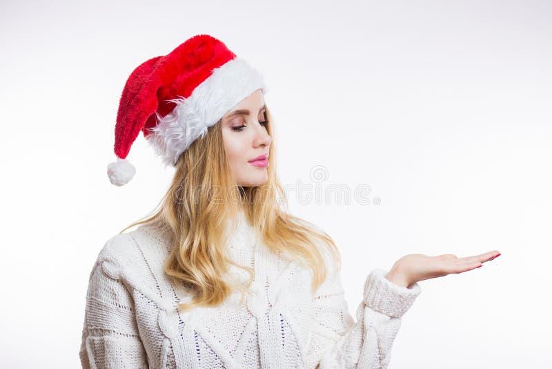 Schöne junge Frau ist das Ihr Produkt des neuen Jahres in einer beige gestrickten Strickjacke über einem weißen Hintergrund stockbild