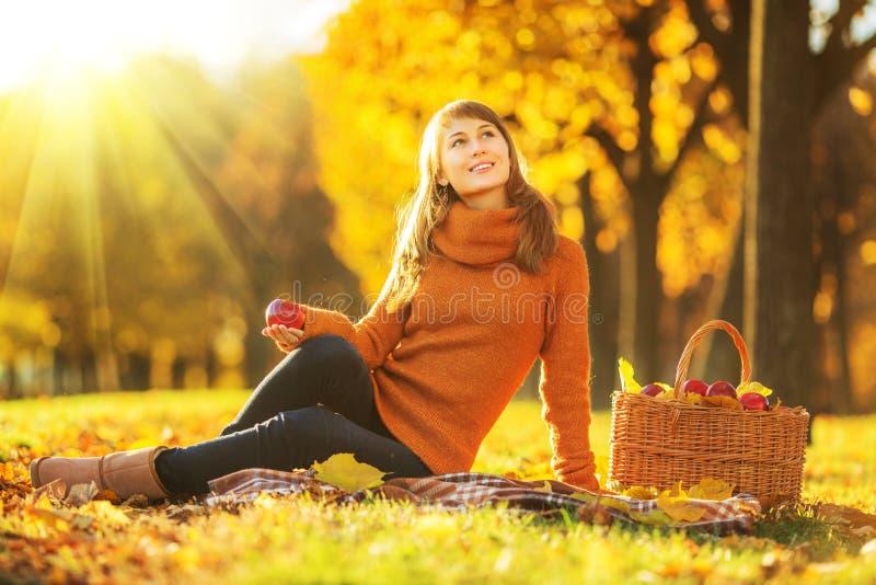 Schöne junge Frau ist, lächelnd sitzend und mit Apfel des reichen Rotes stockfotografie