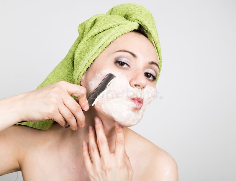 Schöne junge Frau kleidete in den Rasuren eines Badtuches mit einem geraden Rasiermesser an Schönheitsindustrie und Haupthautpfle lizenzfreie stockfotografie