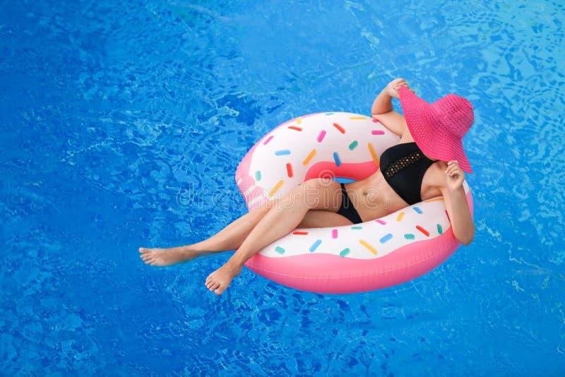 Schöne junge Frau mit aufblasbarem Donut in der blauen Schwimmen stockbild