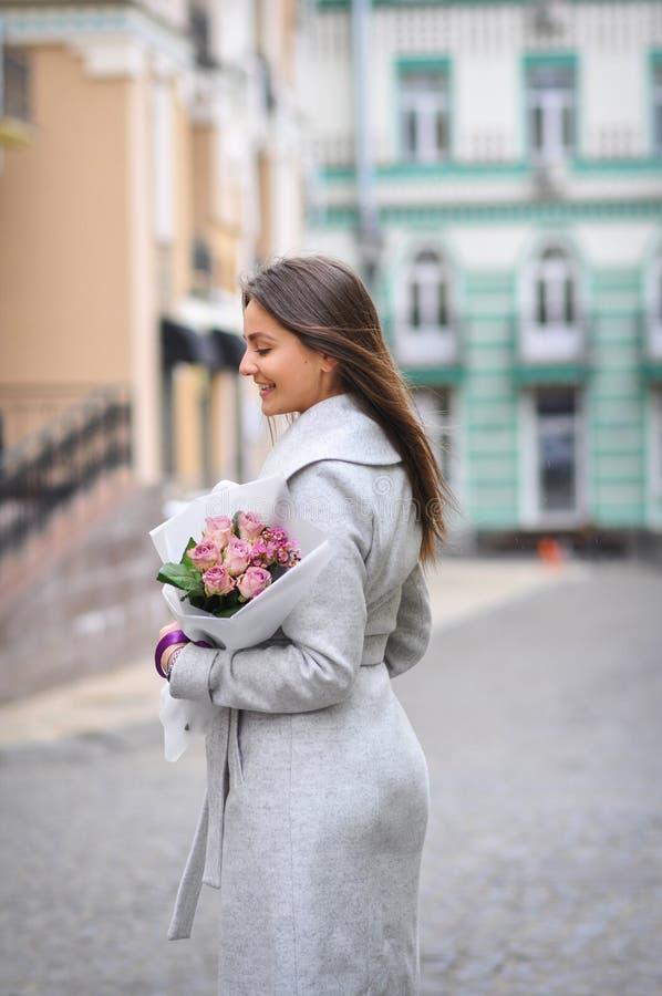 Schöne junge Frau mit Blumenblumenstrauß an der Stadtstraße Frühlingsporträt von recht weiblichem stockfotografie