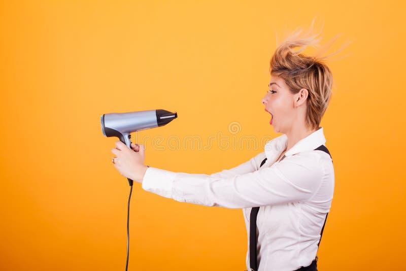 Schöne junge Frau mit dem blonden kurzen Haar unter Verwendung des hairdryer über gelbem Hintergrund lizenzfreie stockfotografie