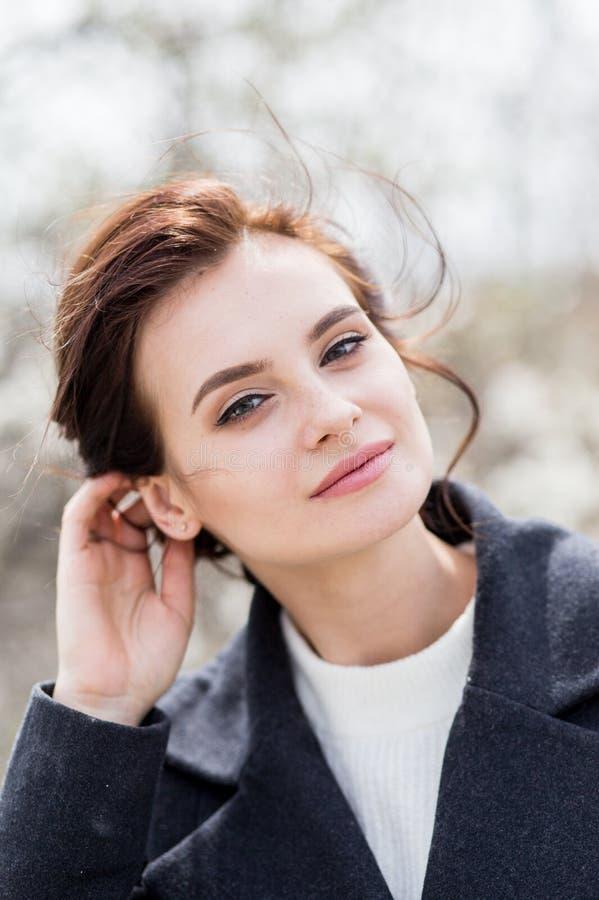 Schöne junge Frau mit dem dunklen Haar im Wollmantel im Freien Frühlingszeitweichheit stockfotos