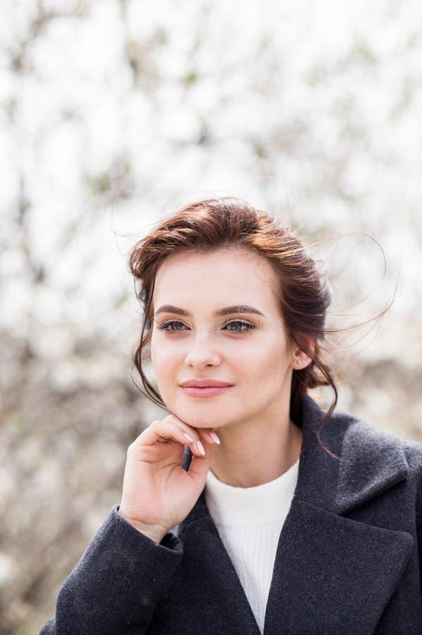 Schöne junge Frau mit dem dunklen Haar im Wollmantel im Freien Frühlingszeitweichheit lizenzfreies stockfoto