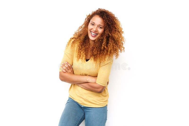 Schöne junge Frau mit dem gelockten Haar lachend mit den Armen gekreuzt gegen weißen Hintergrund stockfoto