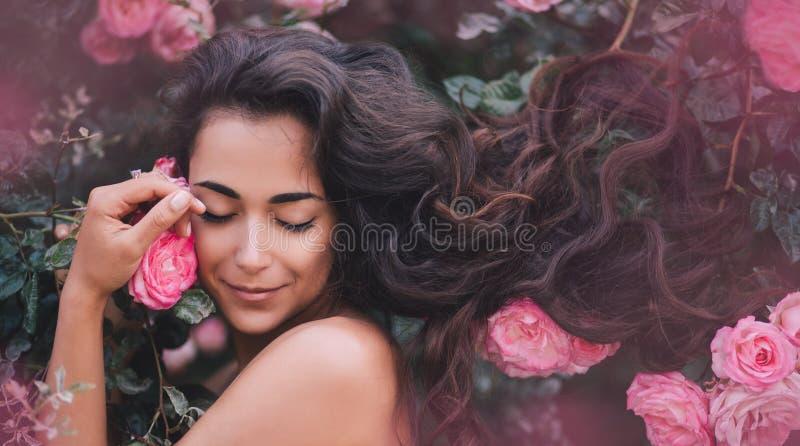 Schöne junge Frau mit dem langen gelockten Haar und perfekter Haut Aufstellung nahe Rosen in einem Garten lizenzfreies stockfoto