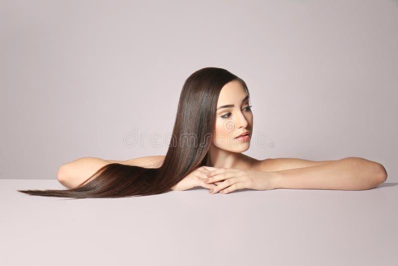 Schöne junge Frau mit dem langen geraden Haar stockfotos