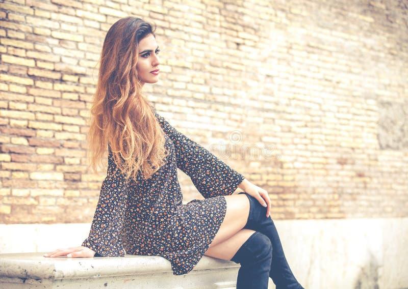 Schöne junge Frau mit dem langen Haar, das auf einer Marmorbank sitzt lizenzfreies stockbild