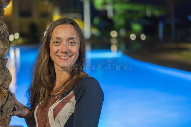 Schöne junge Frau mit dem langen Haar nahe dem Nachtpool lizenzfreie stockfotos