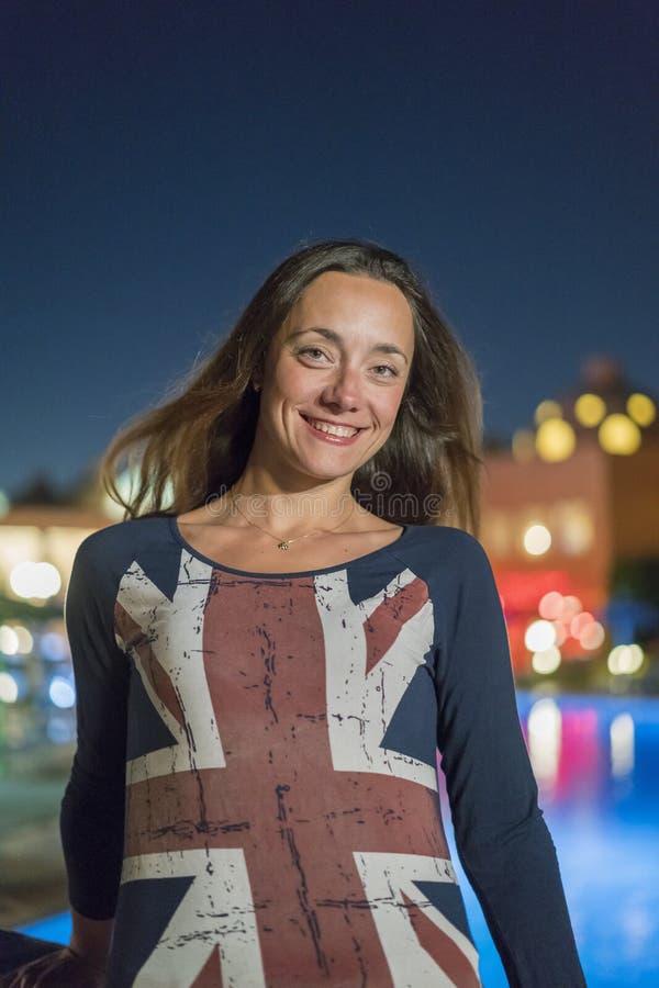 Schöne junge Frau mit dem langen Haar nahe dem Nachtpool Britische Markierungsfahne Vertikales Foto lizenzfreies stockfoto