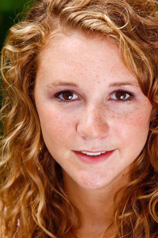 Schöne junge Frau mit dem lockigen Haar, Brown-Augen stockbild
