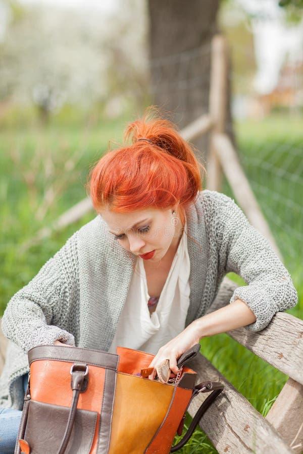 Schöne junge Frau mit dem roten Haar, das draußen auf einer Bank, nach etwas suchend sitzt lizenzfreies stockbild