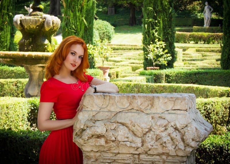 Schöne junge Frau mit dem roten Haar im roten Kleid, das im grünen Sommerpark aufwirft Porträt des schönen Mädchens im Retrostil  stockbild