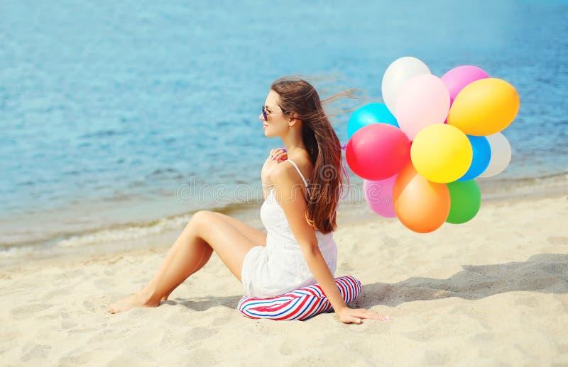 Schöne junge Frau mit den bunten Ballonen, die auf Strand sitzen lizenzfreie stockbilder