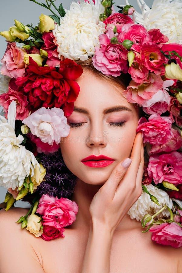 schöne junge Frau mit den geschlossenen Augen, die im Blumenkranz aufwerfen lizenzfreies stockbild